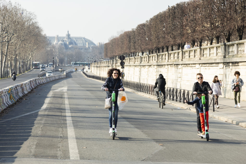 Personnes se déplaçant en trottinettes électriques à Paris, sur la route